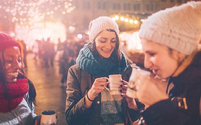 Frauen trinken Glühwein an Glühweinstand wärmend mit Heizpilz mit Propangas
